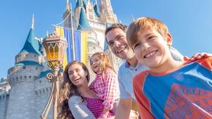 Una familia de 4 espera fuera del Cinderella Castle en el Parque Temático Magic Kingdom de Walt Disney World Resort