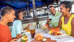 Los Visitantes se ríen sentados a la mesa de un restaurante llena de comidas y bebidas deliciosas.