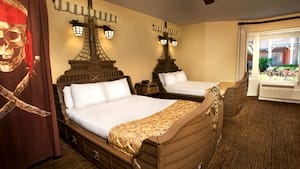 A pirate-themed room at Disney's Caribbean Beach Resort features ship-shaped beds and a Jolly Roger flag