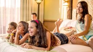 Tres hermanas y su mamá miran TV en la cama mientras el papá se sienta cerca de la ventana de su habitación de Hotel.