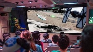 El público sentado frente a la pantalla mira imágenes de una carrera aérea en la cual un cazaTIE persigue y dispara al Millennium Falcon