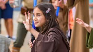A girl dressed in Jedi robes holds a toy light saber in her right hand while raising her left hand upward