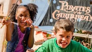 Una niña y un niño gruñen y hacen poses intimidantes de piratas en frente de la atracción Pirates of the Caribbean
