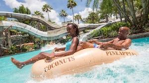 Pai e filha boiam em uma piscina sobre um grande bote inflável