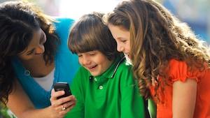 Mãe mostrando um telefone celular a um menino e uma menina