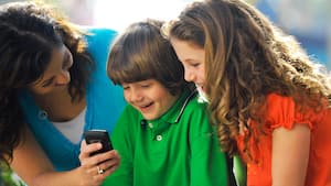 A mother shows a mobile phone to a boy and girl