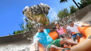 Pai, filho e filha em um bote inflável em uma atração descendo um tobogã aquático sob uma queda d'água