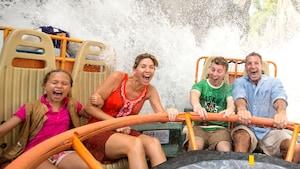 Padre, madre, hija e hijo gritan cuando se salpican con agua en la atracción Kali River Rapids