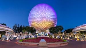 Monotrilhos passam por ambos os lados da Spaceship Earth com a peça central icônica do Epcot acesa à noite