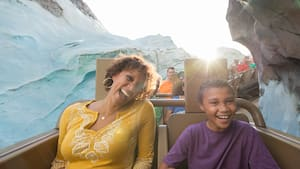 Uma mãe e seu filho sorriem a bordo da atração Expedition Everest – Legend of the Forbidden Mountain