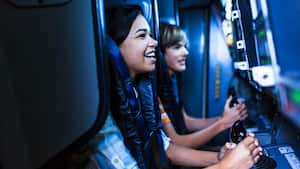 Young Guests gripping sets of controls while experiencing Mission: SPACE in Future World at Epcot