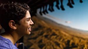 Un joven Visitante sonríe mientras disfruta de Soarin' Around the World en Future World, en Epcot