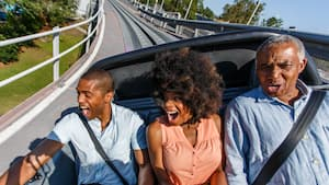 Une famille de visiteurs crie de joie lors d'un tour grisant à bord de Test Track à Future World