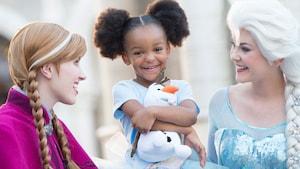 Une visiteuse sourit en serrant une peluche d'Olaf dans ses bras à une expérience de rencontre des personnages avec Anna et Elsa