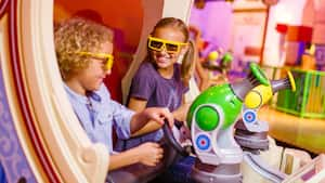 A young brother and sister wearing 3D glasses laugh while they ride and blast aboard Toy Story Mania!
