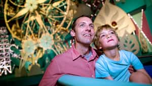 Un père et son fils lancent un regard d'émerveillement à bord de « it's a small world » au parc Magic Kingdom