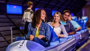 Huéspedes jóvenes adultos bajan las barras de seguridad antes del lanzamiento a bordo de Space Mountain en Tomorrowland