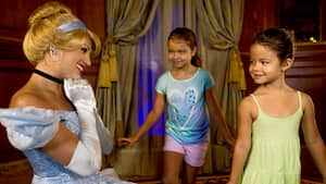 Cinderella smiling elegantly while she greets 2 young female Guests inside Princess Fairytale Hall