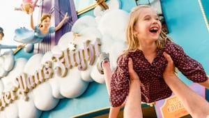 Una joven Huésped sonríe mientras es alzada en el aire por su padre fuera de Peter Pan's Flight