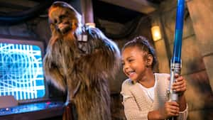An excited young girl plays with a toy lightsaber at a Character Greeting experience with Chewbacca