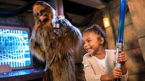 Uma menina animada brincando com um sabre de luz de brinquedo em uma experiência de Encontro com Personagens com o Chewbacca