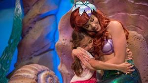 Ariel, a Pequena Sereia, abraçando uma menininha