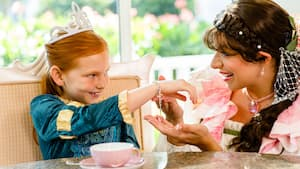 Princess Elena kneels by a table to admire a heart bracelet worn by a girl dressed as a princess