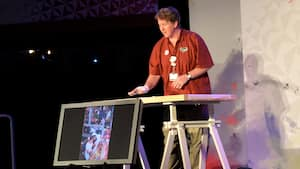 A Disney artist stands behind his drawing table and a large monitor while speaking to an audience