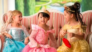 Three young girls in princess costumes on a couch