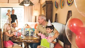 With children and parents looking on, a little boy unwraps birthday gifts at a party