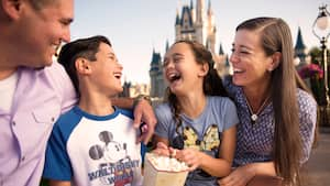 A father, mother, son and daughter laughing while eating popcorn near Cinderella Castle