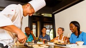 Os convidados animados contemplam enquanto o chef prepara um jantar ornamentado durante o Hibachi Experience