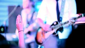 A woman holds her hand up in the air and a musician plays guitar