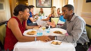 Entre outros Visitantes do Monsieur Paul, um sorridente casal conversa, de mãos dadas, em uma mesa repleta de pratos principais deliciosos, pão crocante e taças de vinho tinto e branco