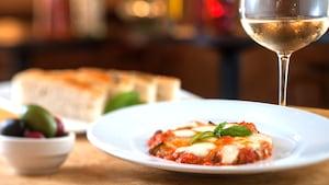 Prato italiano com molho marinara e muçarela, ao lado de uma taça de vinho