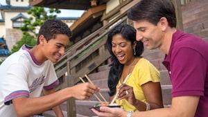 Em uma escadaria com degraus de pedra, em ambiente de estilo japonês, dois jovens seguram hashis na direção de uma travessa com diversos sushis, segurada por outro jovem