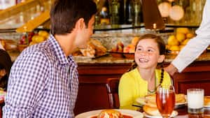 A young girl smiles at her dad while enjoying freshly prepared fare at a Parisian Breakfast event