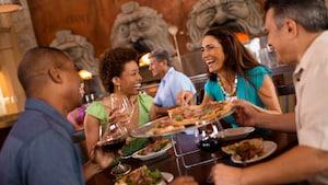 Um homem e uma mulher seguram taças de vinho branco enquanto riem e conversam em um sofá