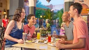 À une table extérieure entourée d'autres dîneurs et de palmiers, un couple et leurs 2fils adolescents rient et discutent en savourant des boissons et de la nourriture appétissante dans un décor de style marocain
