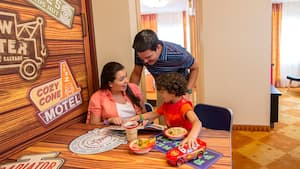 A mother, father and their young son enjoying breakfast together at Disney's Art of Animation Resort