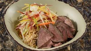 Uma tigela Satu'li com churrasco de carne bovina servido sobre grãos integrais e com molho chimichurri de cebola na brasa