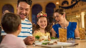 A girl wearing a crown sits at a table in a grand dining room with her mother father and brother