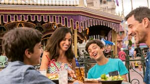 Parents and their 2 boy and girl middle school aged children laugh as they eat lunch near a carousel