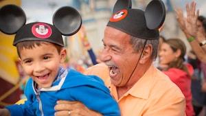 Un hombre sonriente y un niño con orejas de Mickey