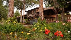 Um Resort com arquitetura rústica perto de um morro florido