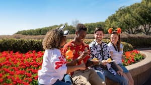 2 men and 2 women seated on the edge of a flower garden at Epcot while they enjoy a snack