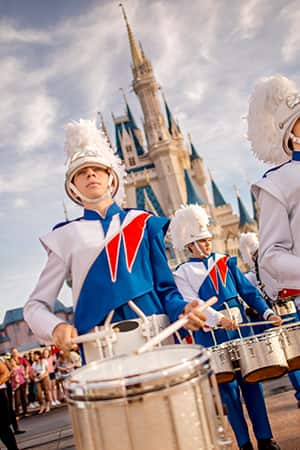 A drumline team perform in front of Sleeping Beauty Castle