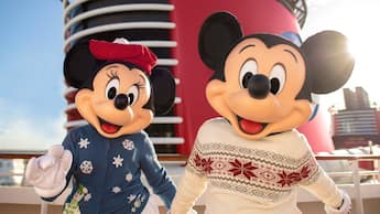 Mickey Mouse and Minnie Mouse dressed in holiday sweaters hold hands on a Disney Cruise Line ship