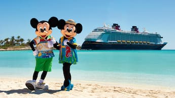 Mickey and Minnie wearing tropical themed attire on a beach in front of a Disney Cruise Line ship