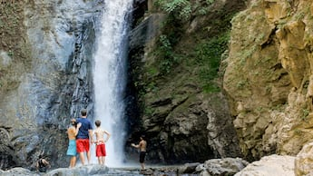 People stand in front of a tall waterfall pouring down a rock face